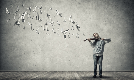 playful behaviour: Teenager boy in empty room playing violin Stock Photo