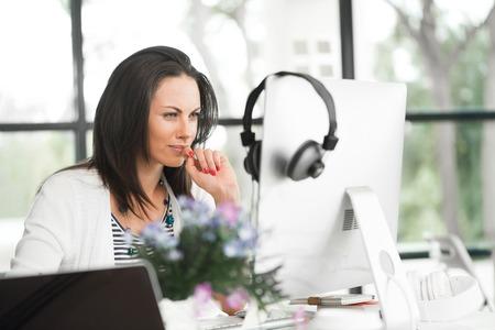 Aantrekkelijke brunette vrouw op kantoor bureau werk aan de computer