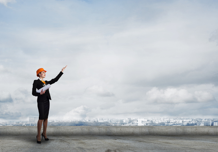 executive helmet: Young woman architect in hardhat holding project in hand Stock Photo