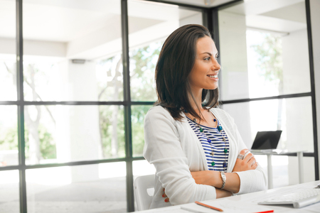 business casual: Thoughtful attractive woman standing with arms crossed on chest