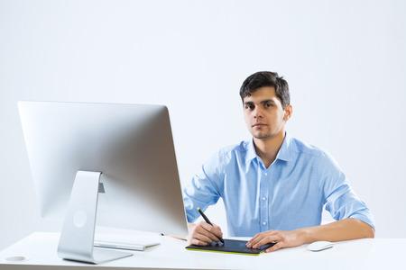 trabajando en computadora: Hombre joven sentado en el escritorio y trabajando en equipo Foto de archivo