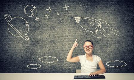 ni�os inteligentes: Chica en edad escolar en los vidrios rojos que se sientan a la mesa y escribiendo en el teclado