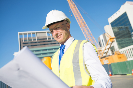 job site: Construction engineer in hardhat with project in hands
