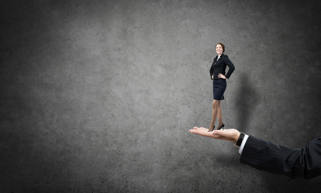 male palm: Big male palm holding small confident businesswoman Stock Photo
