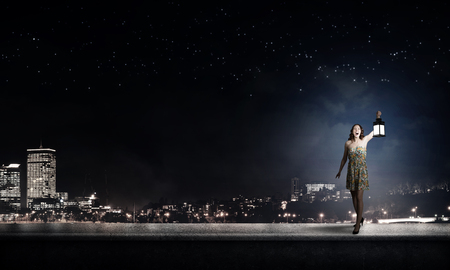 dark city: Young woman in green dress with lantern at night