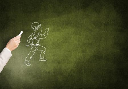 ingeniero caricatura: drawning masculina de la mano con el hombre de la construcci�n tiza en la pizarra Foto de archivo