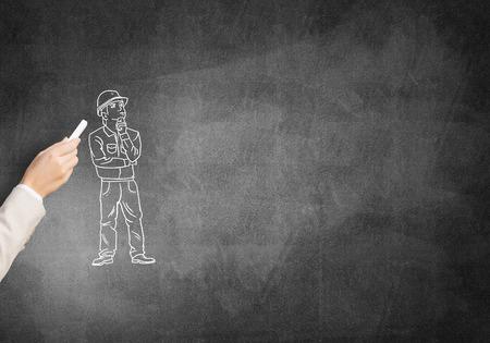 ingeniero caricatura: Male hand drawning with chalk construction man on blackboard