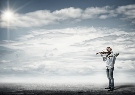 cloudy: Teenager boy playing violin on cloudy sky background