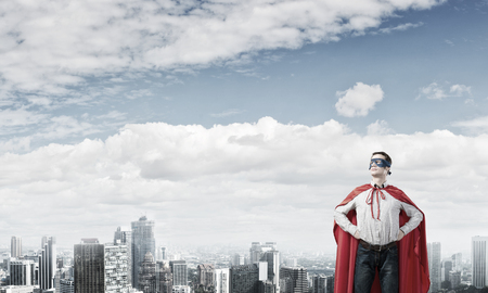 super man: Young super hero man in mask and cape with arms on waist Stock Photo