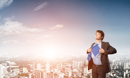 tearing: Office worker opening his shirt like superhero on modern city background