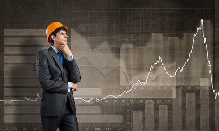 financial concept: Thoughtful engineer wearing helmet and graphs at background