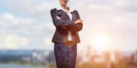 jornada de trabajo: Primer plano de mujer de negocios con los brazos cruzados sobre el pecho en el fondo de la ciudad moderna