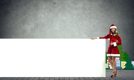 Christmas Santa girl pointing with finger on white blank banner