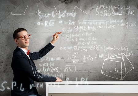 Handsome student sitting at table and drawing on chalkboard