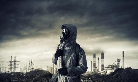 survivor: Man survivor in gas mask on industrial gray background