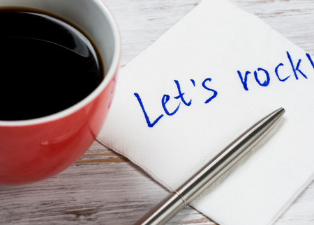 affraid: Cup of coffee and napkin with writings on table Stock Photo