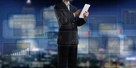 using tablet: Businessman on digital background using tablet finances application Stock Photo