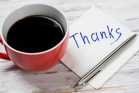 Taza de café y de servilleta con escritos sobre la mesa
