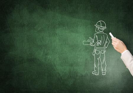 ingeniero caricatura: drawning masculina de la mano con el hombre de la construcción tiza en la pizarra Foto de archivo