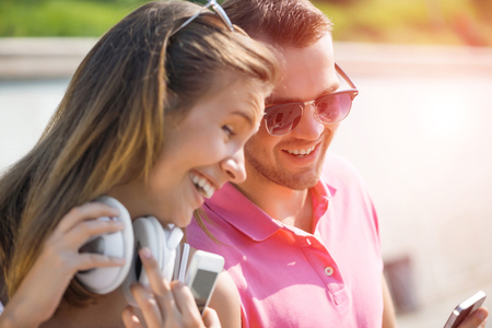 outside shooting: Young smiling couple in summer street using smartphone Stock Photo