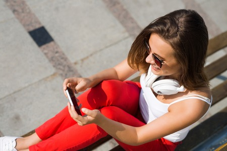 handsfree phones: Top view of young pretty brunette with mobile phone sitting on bench in summer park Stock Photo