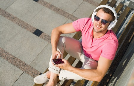view to outside: Top view of smiling man sitting outside with mobile phone and headphones