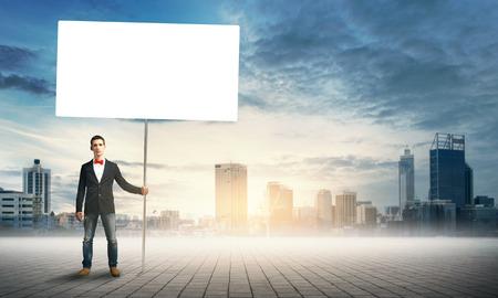 fullbody: Fullbody of handsome guy holding white blank banner