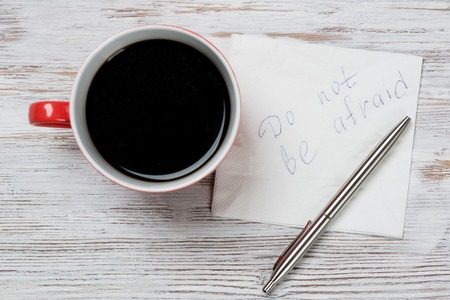 Cup of coffee and napkin with writings on table Stock Photo