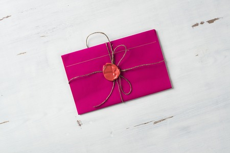 red wax seal: Pink letter envelope with wax seal on wooden surface