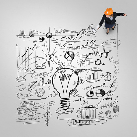 constructor: Vista superior de mujer ingeniero y estrategia de negocios bocetos en el piso Foto de archivo