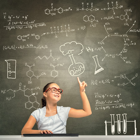 internet education: Girl of school age in red glasses sitting at table and typing on keyboard