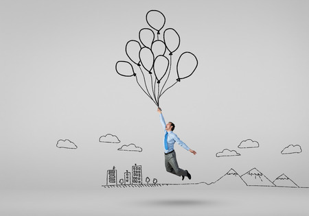 Young successful businessman flies on bunch of drawn balloons