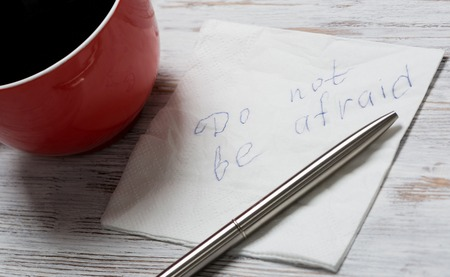 affraid: Cup of coffee and napkin with writings on table
