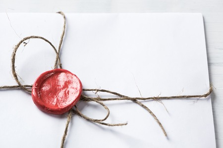red wax seal: Old letter envelope with wax seal on wooden surface