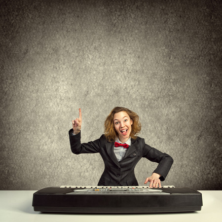finger bow: Funny crazy woman in suit and bow tie playing piano and pointing with finger up Stock Photo
