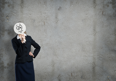 business sign: Businesswoman hiding her face behind round mask