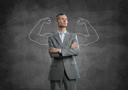 self assured: Businessman with strong arms drawn with chalk behind his back