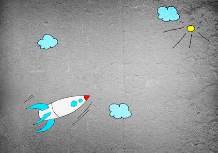 Image de fond avec le vol dessiné roquette sur le mur de ciment Banque d'images