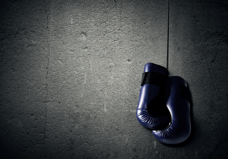 padding: Boxing gloves hanging nailed to wall as concept of retirement