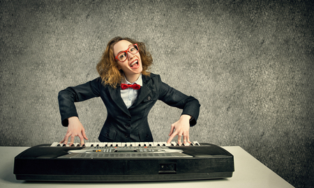loony: Funny crazy woman in suit and bow tie playing piano Stock Photo