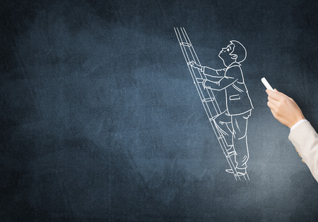 climbing ladder: Female hand drawing with chalk businessman climbing ladder on blackboard