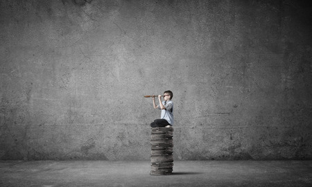 broaden: Kid of school age sitting on pile of books and looking in spyglass