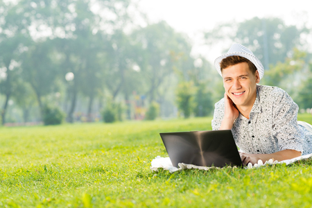 enthusiastically: young man in the park sitting on the grass, enthusiastically working with a laptop