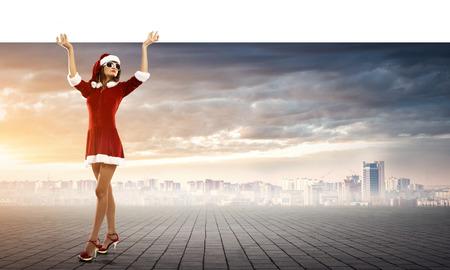 female christmas: Full length of Christmas Santa girl holding white blank banner above head