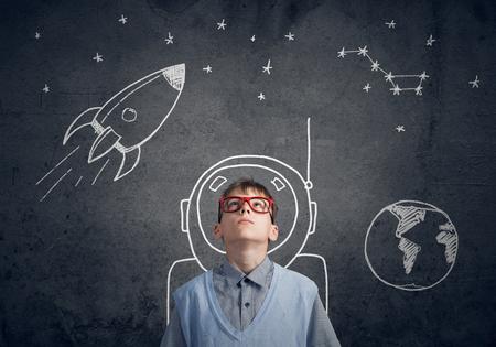 Cute boy d'âge scolaire rêve, il est astronaute Banque d'images - 53850853