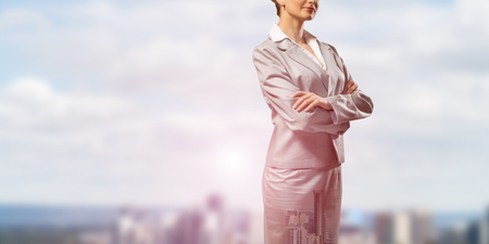 lady boss: Close up of businesswoman with arms crossed on chest on modern city background Stock Photo