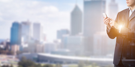 Exposure of modern city and businessman using mobile phone Stock Photo