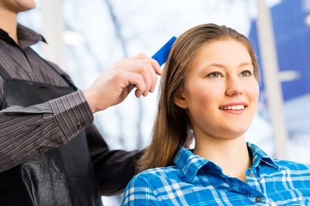 happy customer: male hairdresser puts womans hair in a hairdressing salon