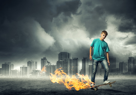 boy skater: Skater boy riding on his skateboard burning in fire Stock Photo
