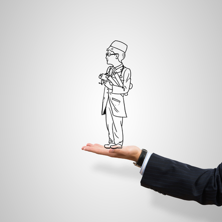 male palm: Drawn businessman in male palm on gray background